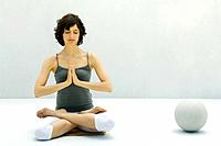 Woman sitting on the ground in lotus position, hands clasped, eyes closed