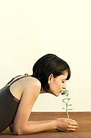 Woman smelling sedum plant, eyes closed, side view