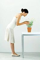 Woman smelling potted chamomile plant, eyes closed, side view