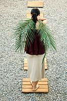 Woman standing on foothpath, carrying palm leaves behind back, rear view