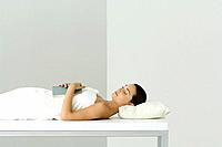 Woman lying on massage table, holding book on chest, eyes closed