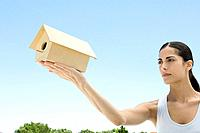 Woman holding up birdhouse