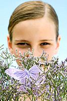 Girl looking over flowering bush with fake butterfly