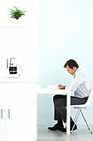 Man sitting at desk, working, coffee maker on counter in foreground