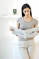 Woman leaning against counter, reading newspaper