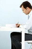 Man sitting at table, writing, side view