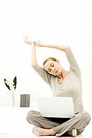Woman sitting cross-legged in office, stretching, laptop computer on her lap