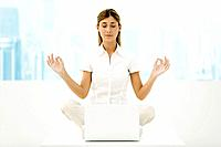 Woman sitting in lotus position in front of laptop computer, eyes closed
