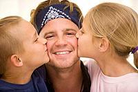 children kissing dad on cheeks