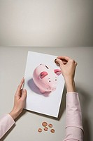 A woman holding a photograph of a piggy bank and money