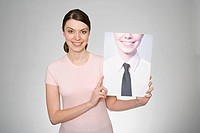 A woman holding a photograph of herself