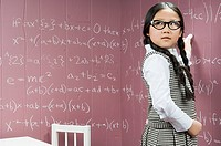 A girl writing mathematical formula on a wall