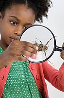 A girl looking at a beetle with a magnifying glass