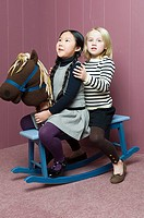 Friends playing on a rocking horse