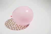 Thumbtacks under a pink balloon