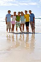 Group of teenagers 14-16 arm in arm on beach, smiling, portrait