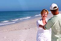 Senior couple holding hands on beach, smiling at each other