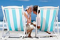 Mature couple on deck chairs on beach preparing to kiss, rear view