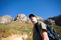 Young man hiking with rucksack, low angle view