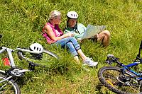 Mature couple in grass by bicycles, looking at map