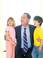 Businessman embracing son and daughter 4-8, smiling