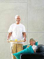Mature couple, man with breakfast tray by woman with glass of juice on sofa, smiling, portrait