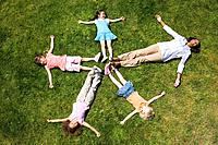 Woman with girls 4-8 lying on grass making star shape