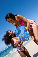 Mother and daughter4-6 with fishing net on beach tilt