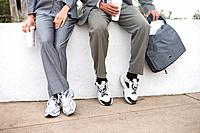Businessmen in sports shoes on wall with disposable cups, low section