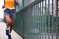 Woman running by fence, low section