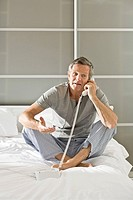 Man on bed using telephone (thumbnail)