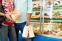 Couple with gift boxes and shopping bags in bakery, mid section