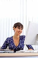 Woman at computer, smiling