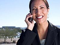 Native American businesswoman talking on cell phone outdoors