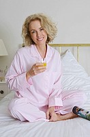 Woman on bed with orange juice