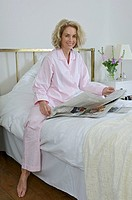 Woman on bed with newspaper