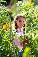 Girl 8-10 in vegetable garden, portrait