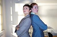 Businesswomen back to back, portrait