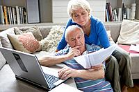 Senior couple with laptop computer and paperwork in living room