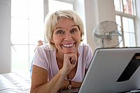 Senior woman with laptop computer, smiling, portrait