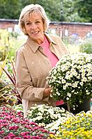 Woman with plant in garden center, smiling, portrait