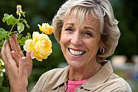 Mature woman tending rose bush, smiling, portrait