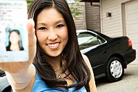 Asian teenager proudly showing new driver&#8217;s license