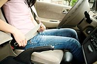 Asian teenager buckling seat belt