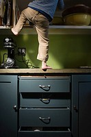 Boy climbing in kitchen