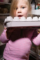 Little girl with egg carton