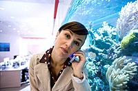 Businesswoman on telephone by fish tank, portrait