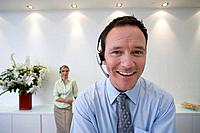 Businessman with headset, smiling, portrait