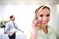 Businesswoman with headset, smiling, portrait, colleague in background