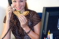 Woman on telephone at desk with sandwich, smiling, portrait